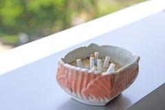 桃红色烟灰缸在桌被安置 免版税库存照片