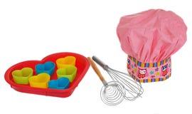 桃红色烹调帽子,有多彩多姿的样式、心脏、花和猫头鹰的 曲奇饼的心脏模子在红色 扫生泡沫 库存照片