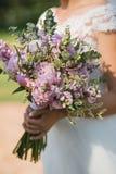 桃红色牡丹、玫瑰和野花美丽的典雅的夏天婚礼花束在新娘的手上 免版税库存图片