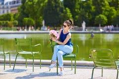 桃红色牡丹的年轻巴黎人妇女在Tuileries 库存图片