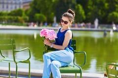 桃红色牡丹的年轻巴黎人妇女在Tuileries 免版税库存照片