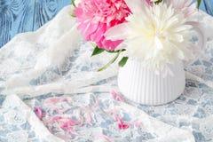 桃红色牡丹美丽的花束在一根花瓶和鞋带的在白色 免版税库存照片