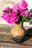 桃红色牡丹花束在土气木桌上的黏土水罐开花 免版税库存照片