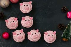 桃红色猪杯形蛋糕-用蛋白质奶油和蛋白软糖装饰的自创杯形蛋糕塑造了滑稽的piggies 免版税库存照片