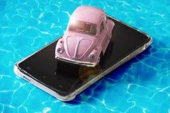 桃红色玩具汽车在一个游泳池的大海的移动电话在一个晴天 图库摄影