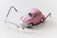 桃红色玩具汽车在一张白色书桌上在镜片附近 库存照片