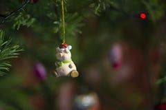 桃红色玩具-在一个红色盖帽的腮腺炎有一条绿色围巾的在一棵绿色新年树垂悬 免版税库存照片
