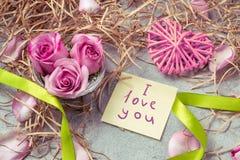 桃红色玫瑰、心脏和笔记与题字我爱你在爱和关心的桌这概念 图库摄影