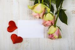 桃红色玫瑰、心脏和纸祝贺的 免版税库存图片