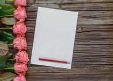 桃红色玫瑰、箱子和铅笔行有纸的 免版税图库摄影