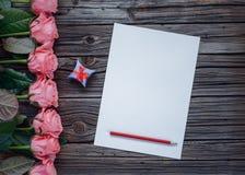 桃红色玫瑰、箱子和铅笔行有纸的 免版税库存图片