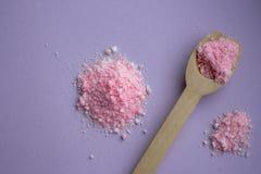 桃红色玫瑰与木匙子的腌制槽用食盐在淡紫色背景 芳香温泉概念 芳香疗法 免版税库存图片