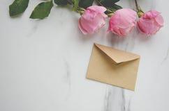 桃红色玫瑰和一个工艺信封在大理石桌上 问候的概念 免版税库存照片