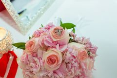 桃红色玫瑰和婚戒婚礼花束在一张木桌上 复制空间 婚礼、党、的爱和的家庭的概念 免版税图库摄影