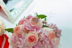 桃红色玫瑰和婚戒婚礼花束在一张木桌上 复制空间 婚礼、党、的爱和的家庭的概念 免版税库存图片