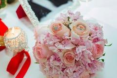 桃红色玫瑰和婚戒婚礼花束在一张木桌上 复制空间 婚礼,党,爱的概念和 免版税库存照片