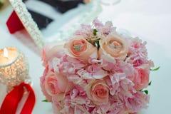 桃红色玫瑰和婚戒婚礼花束在一张木桌上 复制空间 婚礼,党,爱的概念和 免版税图库摄影