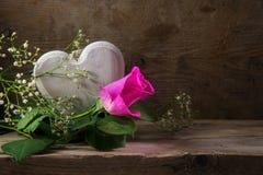 桃红色玫瑰和心脏在一张土气木桌上,拷贝空间在Th 免版税图库摄影