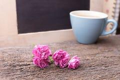 桃红色玫瑰和杯子用咖啡在木头 免版税库存照片