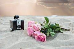桃红色玫瑰和照相机在沙子 库存图片