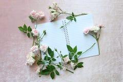 桃红色玫瑰和笔记本 免版税库存照片