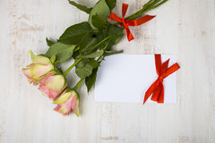 桃红色玫瑰和纸祝贺的 库存图片