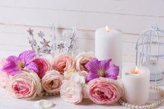桃红色玫瑰和紫罗兰色铁线莲属开花,在白色的蜡烛求爱 免版税库存图片