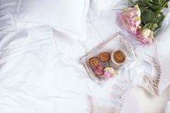 桃红色玫瑰咖啡和花束在床、浪漫史和舒适上 古色古香的企业咖啡合同杯子塑造了新鲜的早晨好老笔场面打字机 早餐在河床上 复制空间 图库摄影