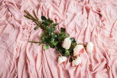 桃红色玫瑰在精美桃红色丝织物说谎 免版税库存照片
