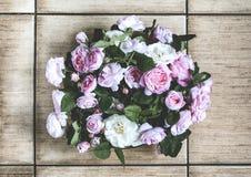 桃红色玫瑰小花束在一个花瓶的在地板上 库存照片