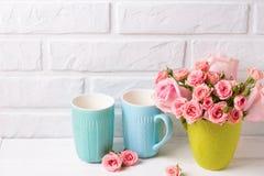 桃红色玫瑰花和明亮的蓝色杯子反对白色砖wa 图库摄影