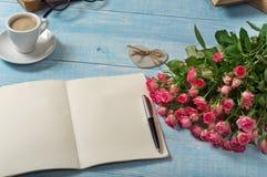 桃红色玫瑰花束与一个开放笔记本的 免版税库存照片