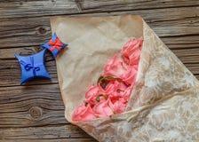 桃红色玫瑰被包裹的花束与华伦泰礼物的 免版税图库摄影