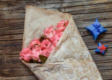 桃红色玫瑰被包裹的花束与华伦泰礼物的 库存图片