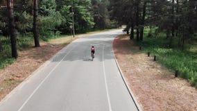 桃红色球衣和黑盔甲的年轻可爱的嬉戏白种人妇女骑她的在嘘夏天森林空中寄生虫的自行车 股票视频