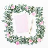 桃红色瓣和玉树花卉花圈框架与笔记本和笔在白色背景 平的位置,顶视图 库存照片