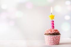 桃红色生日杯形蛋糕有蜡烛与Bokeh的光背景 库存照片