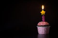 桃红色生日杯形蛋糕有蜡烛黑暗背景 免版税库存照片