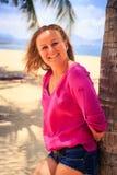 桃红色的亭亭玉立的哀伤的女孩在棕榈倾斜反对沙子和海 免版税库存照片
