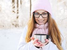 桃红色的可爱的愉快的年轻白肤金发的妇女编织了帽子围巾获得乐趣喝从热水瓶杯子多雪的冬天公园森林的热的茶 免版税图库摄影