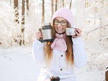 桃红色的可爱的愉快的年轻白肤金发的妇女编织了帽子围巾获得乐趣喝从热水瓶杯子多雪的冬天公园森林的热的茶 免版税库存照片