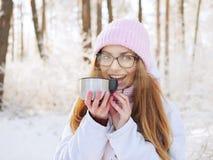 桃红色的可爱的愉快的年轻白肤金发的妇女编织了帽子围巾获得乐趣喝从热水瓶杯子多雪的冬天公园森林的热的茶 库存照片