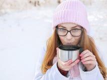 桃红色的可爱的愉快的年轻白肤金发的妇女编织了帽子围巾获得乐趣喝从热水瓶杯子多雪的冬天公园森林的热的茶 图库摄影