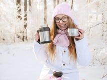 桃红色的可爱的愉快的年轻白肤金发的妇女编织了帽子围巾获得乐趣喝从热水瓶杯子多雪的冬天公园森林的热的茶 免版税库存图片