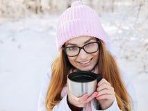 桃红色的可爱的愉快的年轻白肤金发的妇女编织了帽子围巾获得乐趣喝从热水瓶杯子多雪的冬天公园森林的热的茶 库存图片