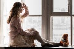 桃红色的女孩由窗口 免版税库存图片
