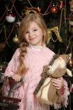桃红色的小女孩在圣诞树 库存图片