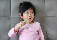 桃红色的小女孩在沙发掠过的牙 库存图片