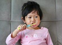 桃红色的小女孩在沙发掠过的牙 免版税库存图片