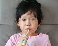 桃红色的小女孩在沙发掠过的牙 免版税库存照片